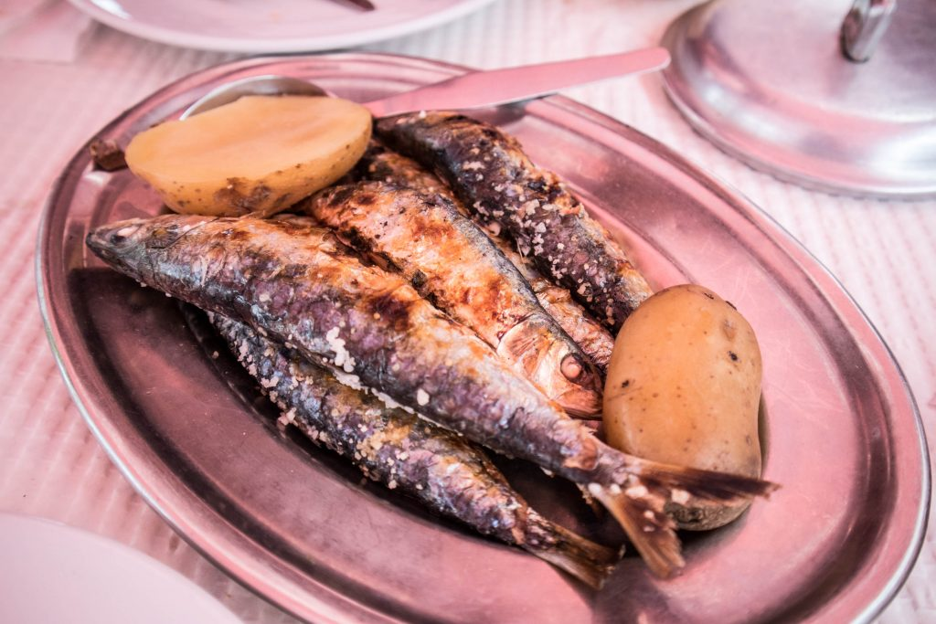 grilled sardines with potatoes on a pink plate in a tasca in cacilhas, lisbon