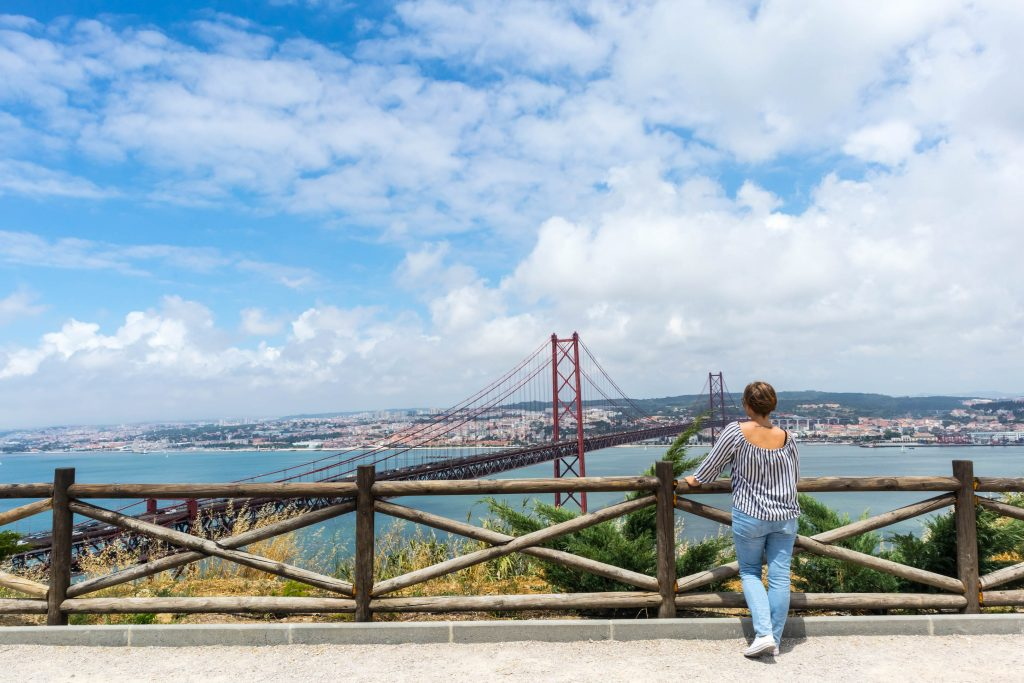 a girl dressed in black and white top and blue jeans stands with her back to the camera and looks at the 25th of april bridge in lisbon from a viewpoint in christo rei