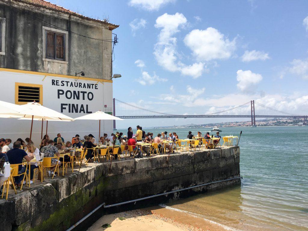 ludzie siedza przy solikach ponto final w lizbonie