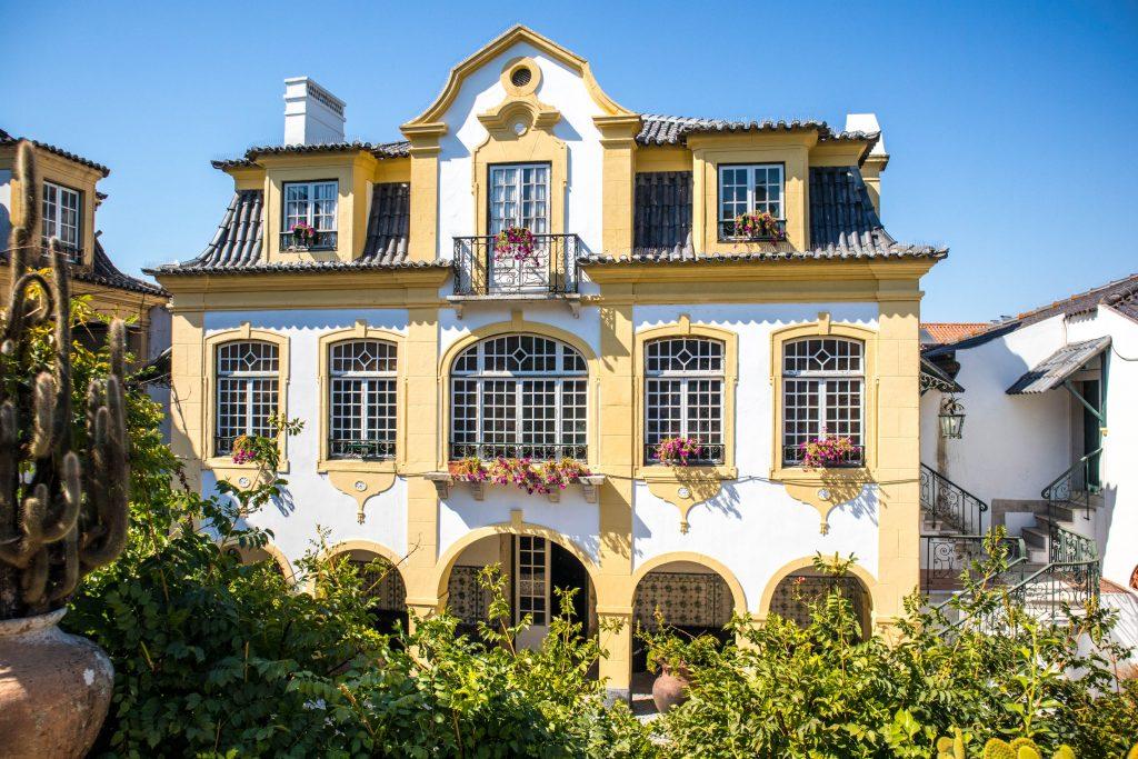 Zółto-biały dom José Maria de Fonseca w Azeitao otoczony roślinnością w słoneczny dzień.