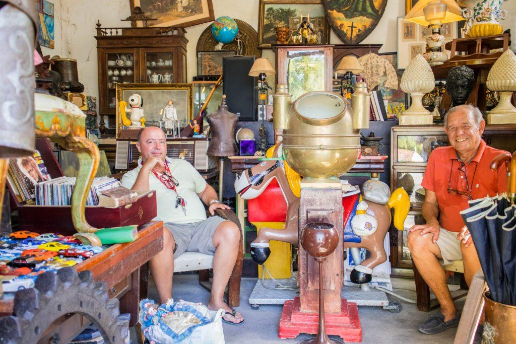 Dwoch opalonych mezczyzn w letnich ubraniach siedzi w sklepie ze starociami w Azeitao.