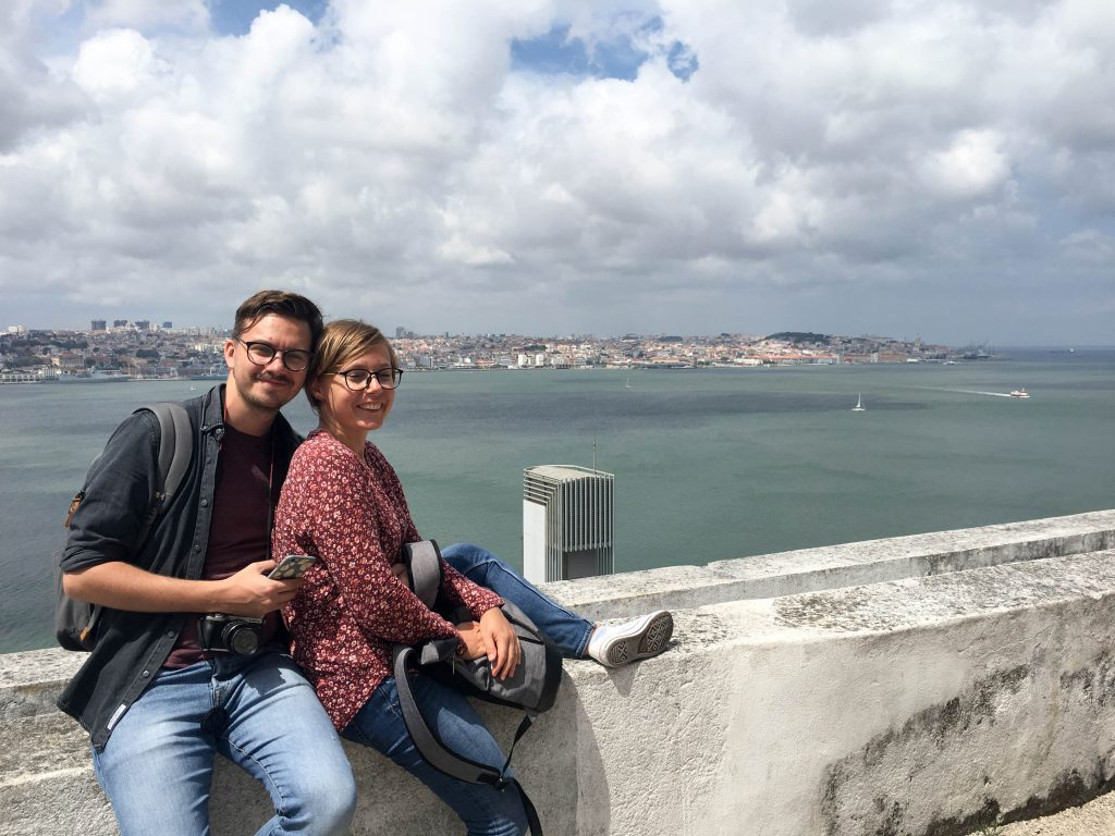 a couple sits on a wall on a viewpoint in almada lisbon