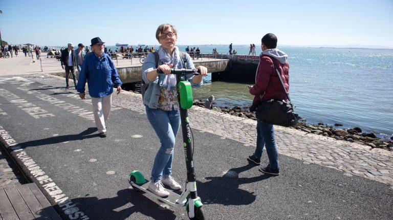 dziewczyna na hulajnodze lime w sloneczny dzien w lizbonie przy rzece