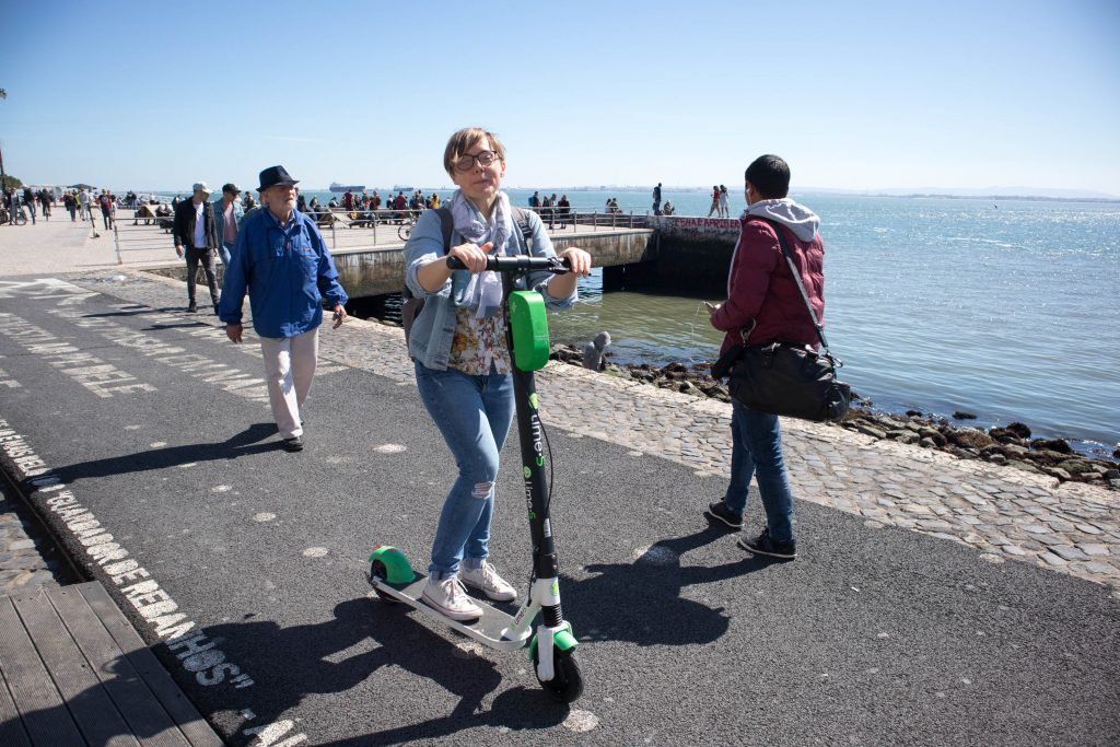 a girl on a lime scooter on a sunny day at the river in lisbon
