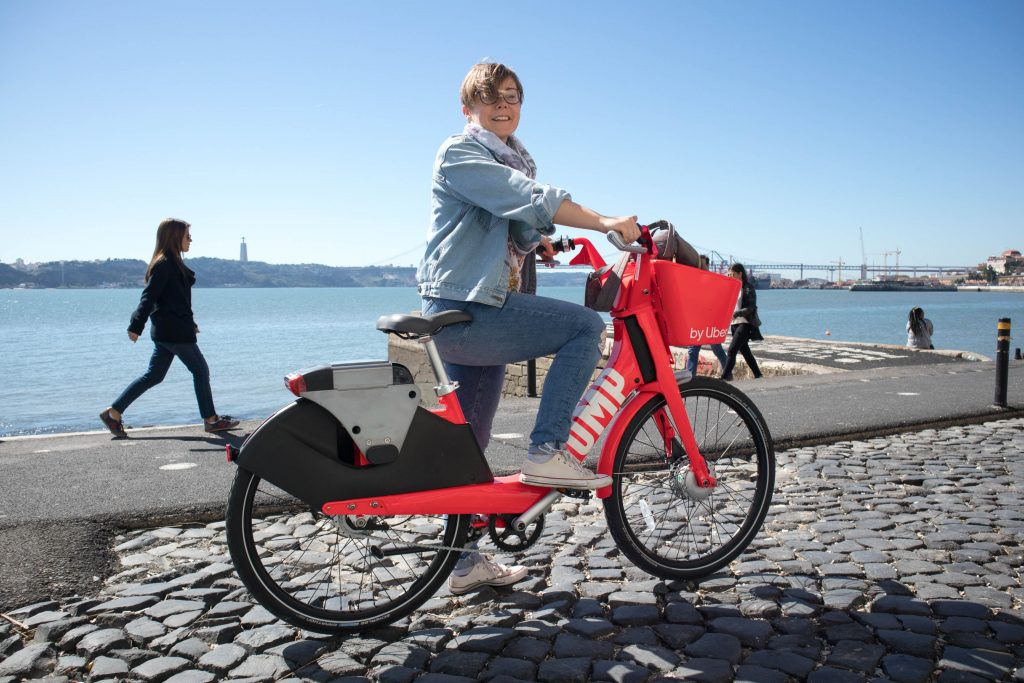 a smiling girl on a red uber bike at the river in lisbon