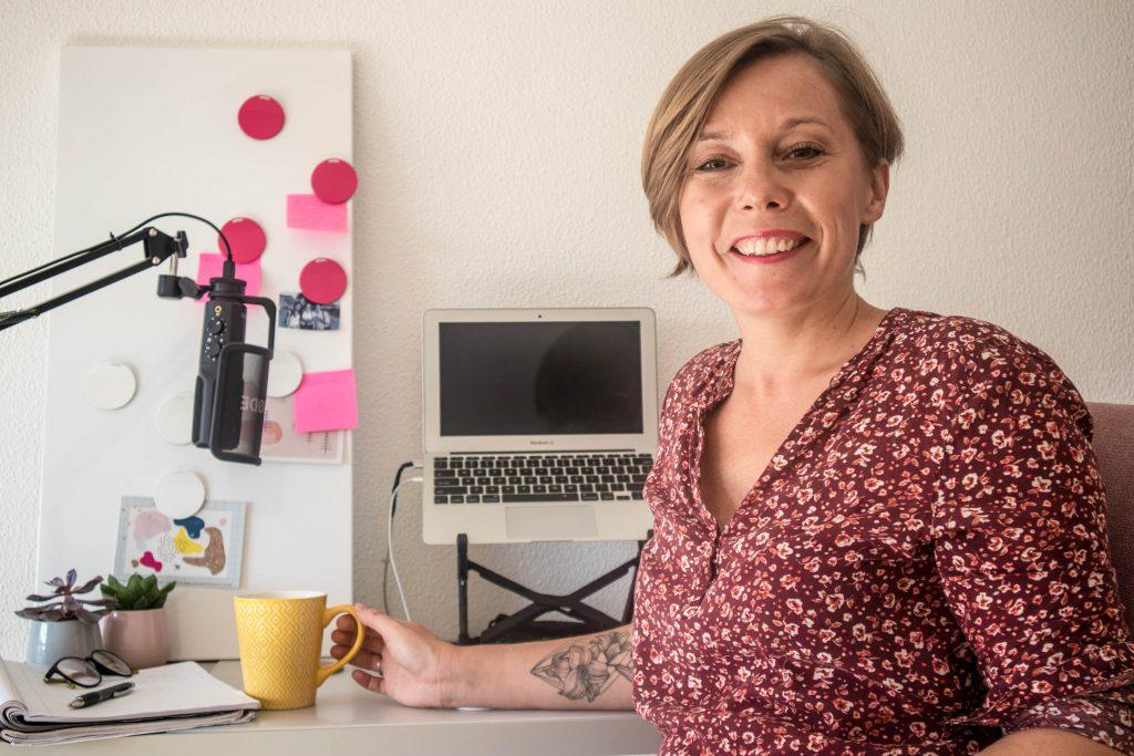 nauczycielka online siedzi przy biurku z zoltym kubkiem goracej kawy