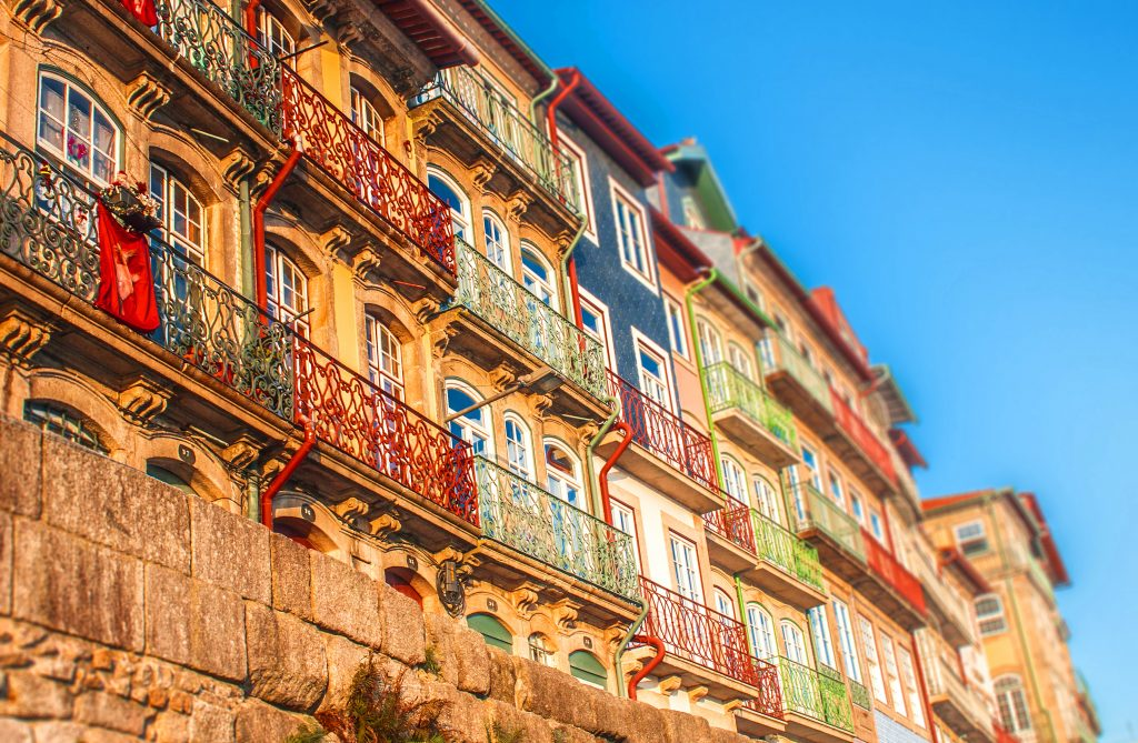 kolorowe domy w Porto z małymi balkonami w słoneczny dzien. Przprowadzka do Porto.