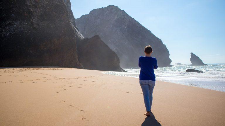 dziewczyna odchodzi w strone slonca na plazy adraga w portugalii