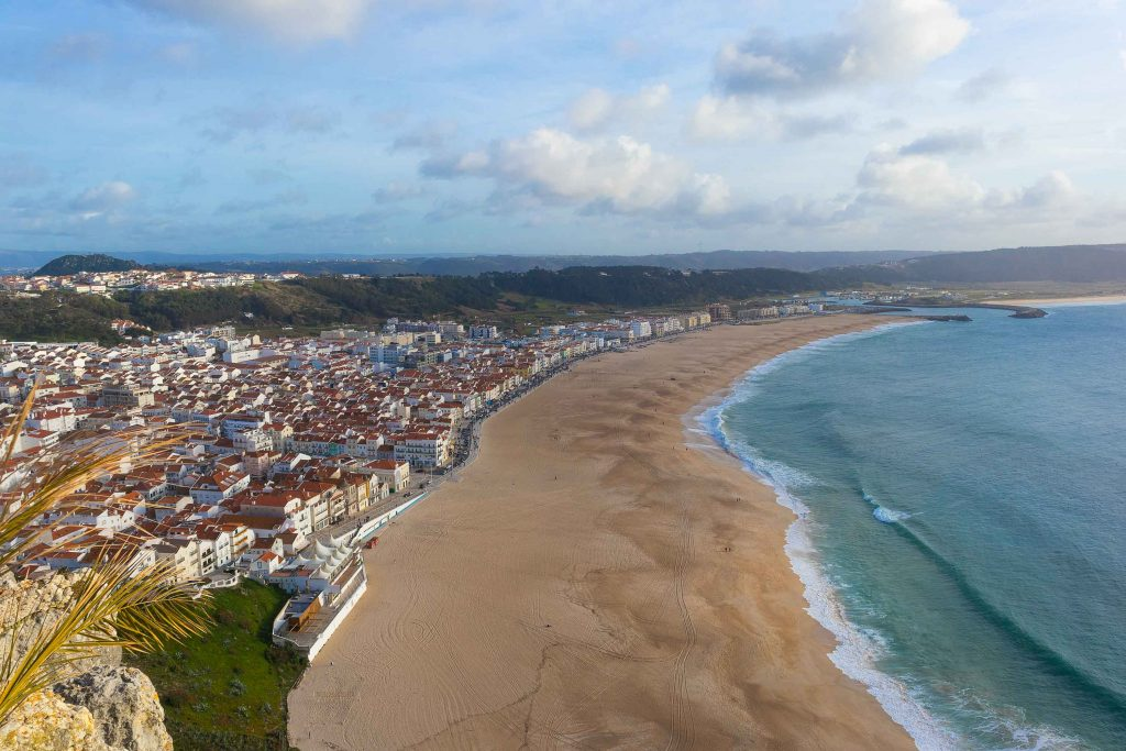 a beach in nazare portugal seen from a top of a cliff