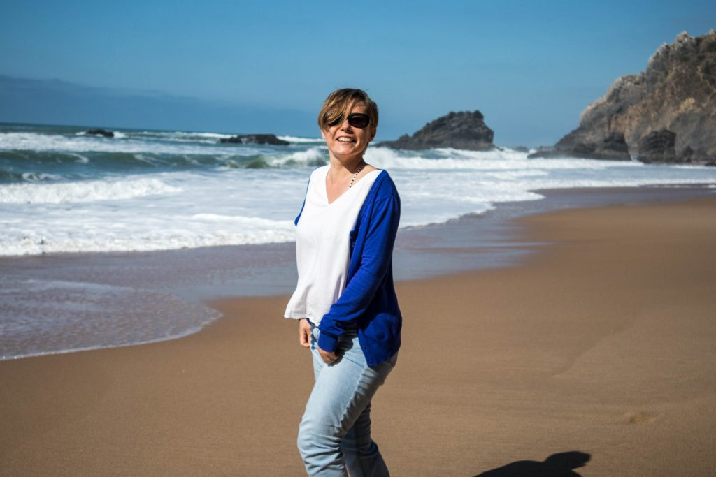 a girl in a blue jumper laughs on adraga beach in portugal