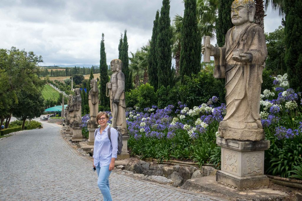 a girl standing among flowers in buddha garden in portugal
