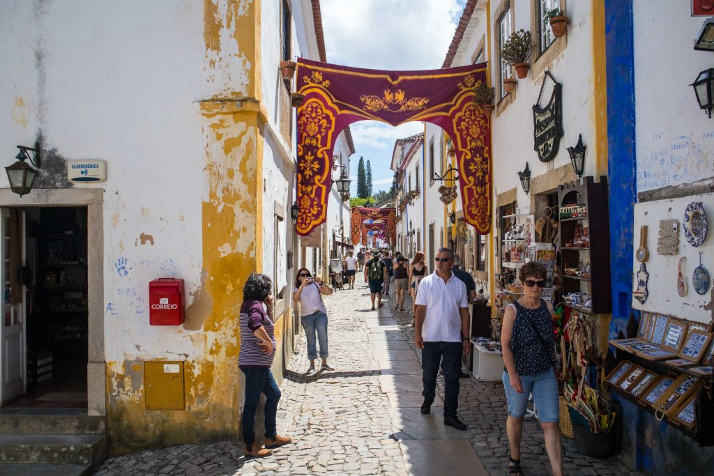 a street in obidos with hanging banners and people walking