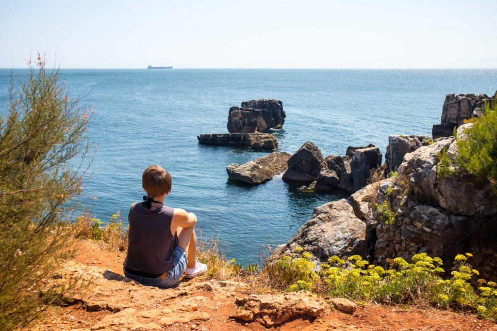 dziewczyna siedzi na skałach przy plazy guincho
