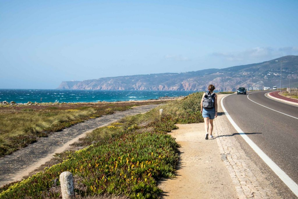 a girl walks from cascais to guincho by the side of the road with the ocean on her left.