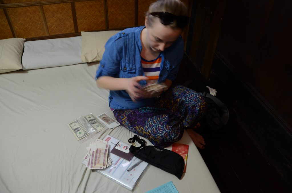 a girl is sitting on a matress counting money