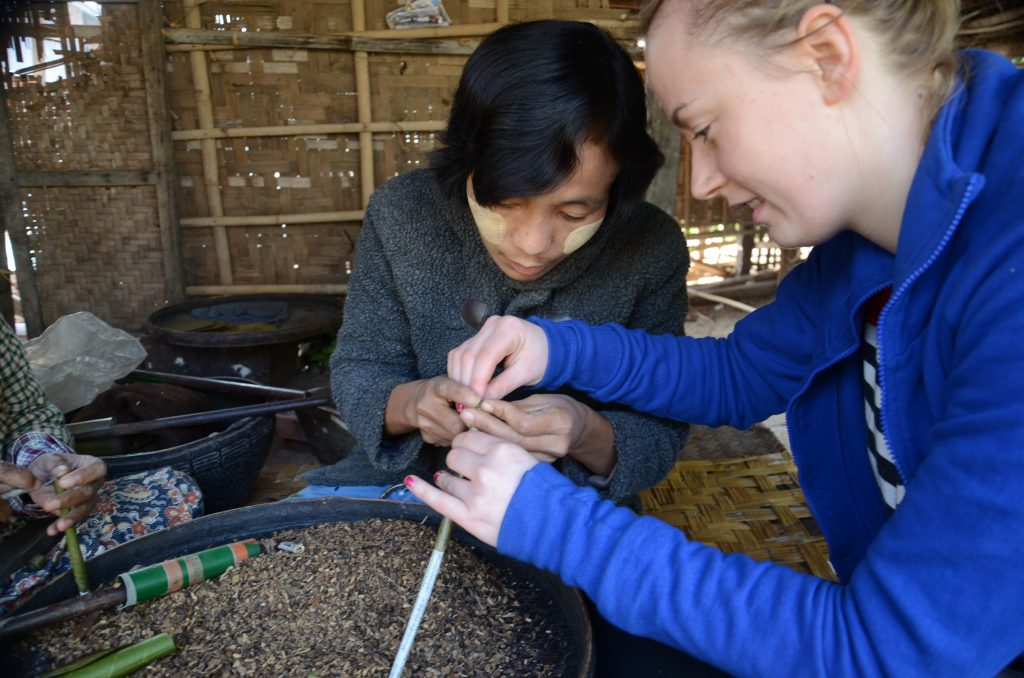 a girl in a blue jumper is making a cigar with a burmese lady