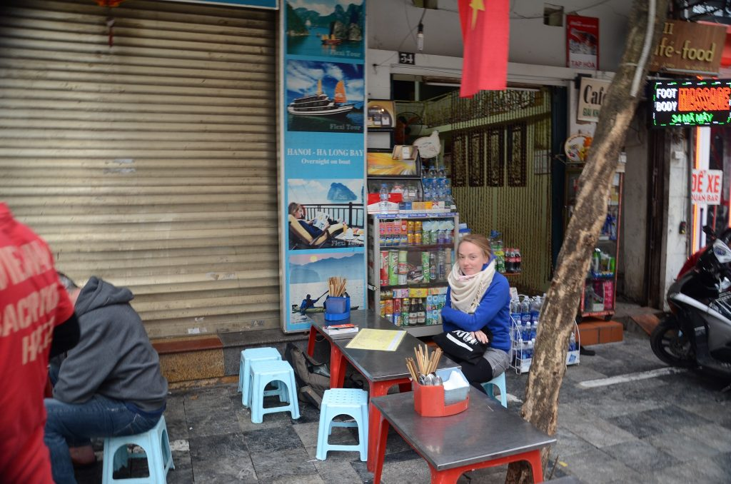 a girl in a blue jumper sits at a table in a vietnamese restaurant