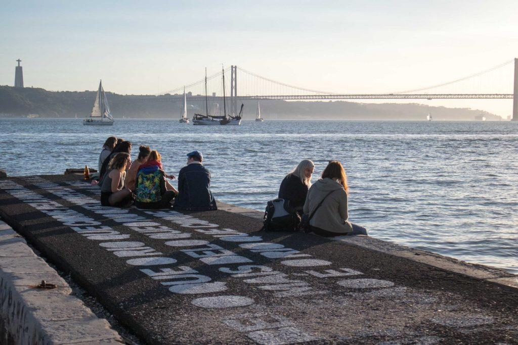 brzeg rzeki tag o zachodzie słonca, ludzie siedza na brzegu i patrza na lodzie i most