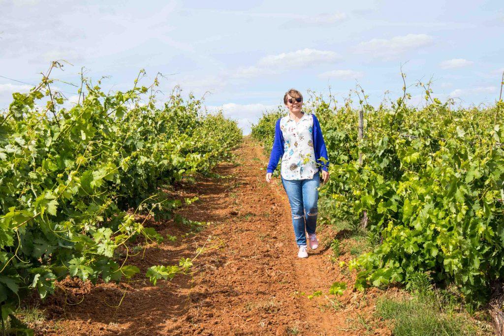 usmiechnieta dziewczyna w niebieskim sweterku idzie wzdluz winorosli w alentejo
