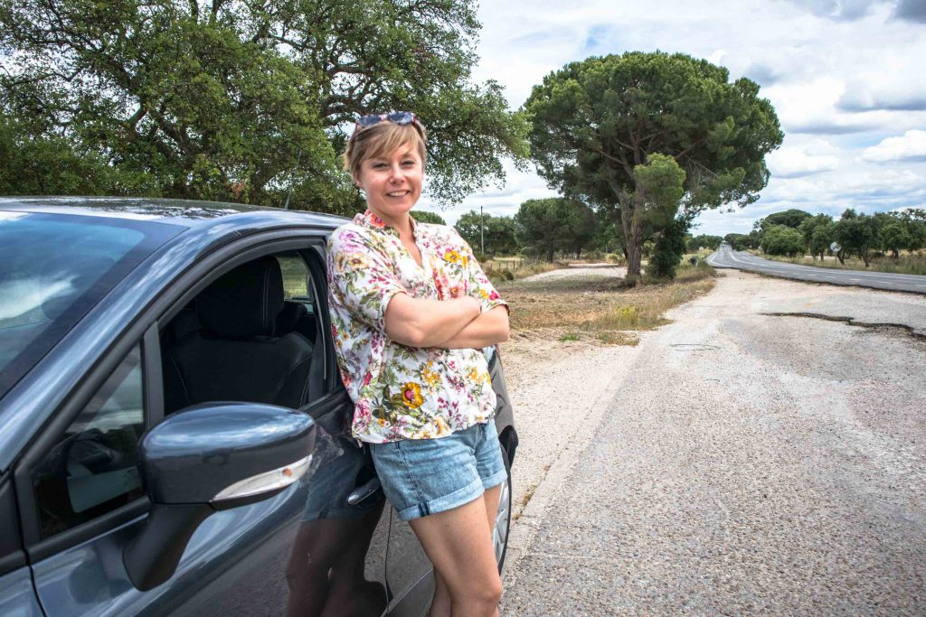 a girl standing next to a car on an anlentejo road
