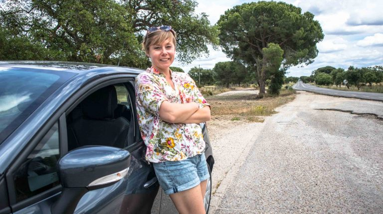 dziewczyna stoi obok samochodu na drodze w portugalii