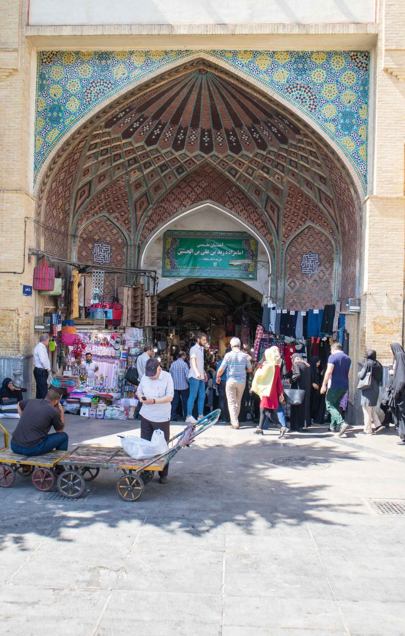 market in teheran with crowds of people in front of mosque
