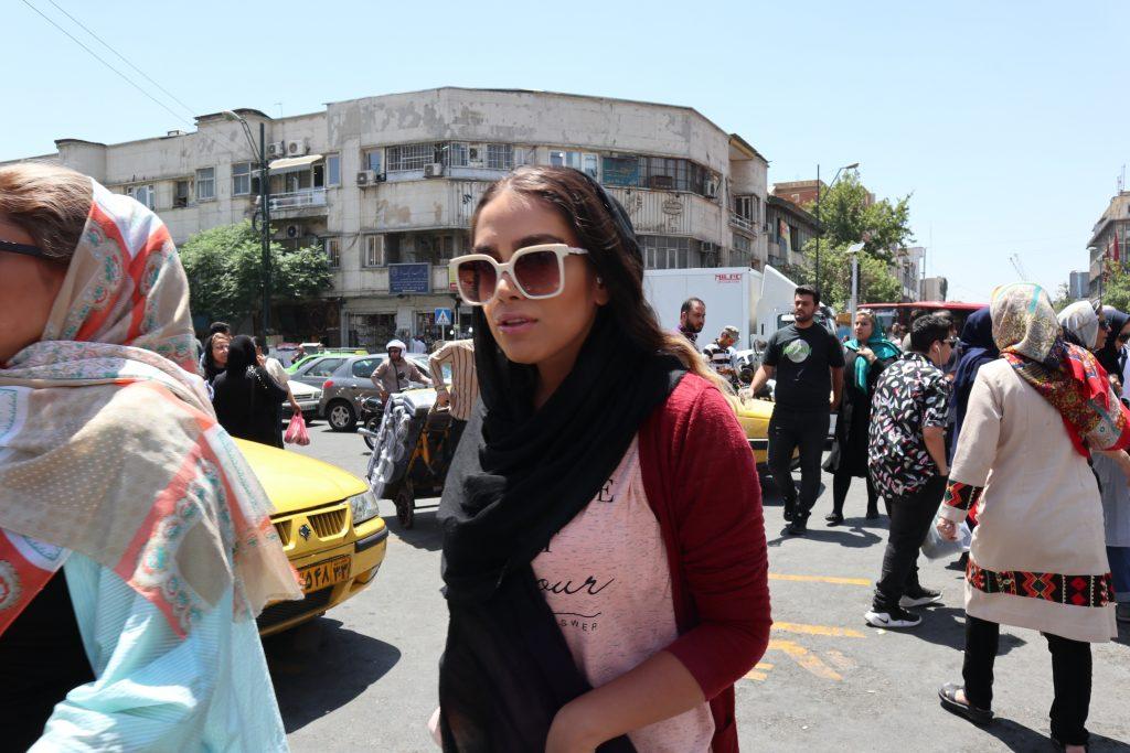mloda iranka w slonecznych okularach na zatloczonej ulicy w teheranie