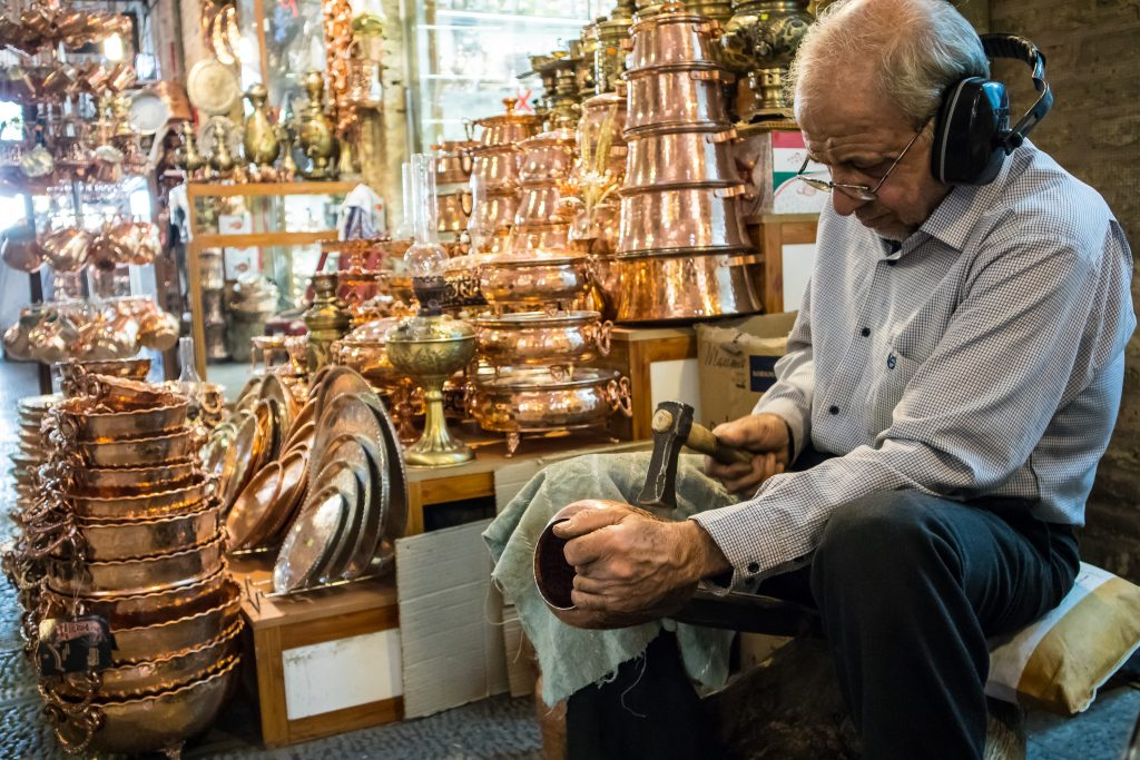 Mężczyzna produkujący garnki na bazarze w Esfahan, w Iranie.