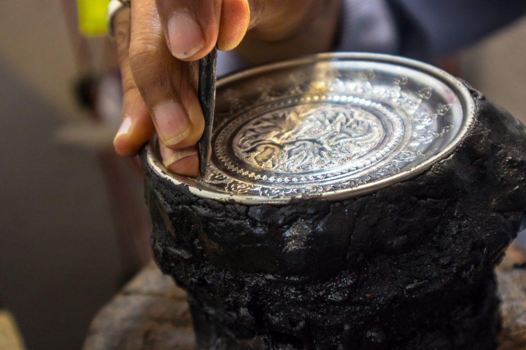 Ręka mężczyzny trzymającego gwóźdź i wyrabiającego srebrne wzory w naczyniu na bazarze w Esfahan, w Iranie.