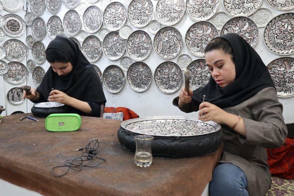 dwie młode iranki pracują nad rzeźbami ze srebra w warsztacie w Esfahan