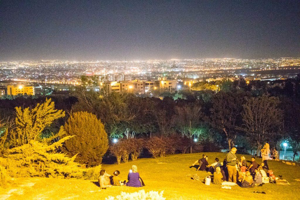 Ludzie siedzą w nocy na górze Soffeh w Esfahan w Iranie.
