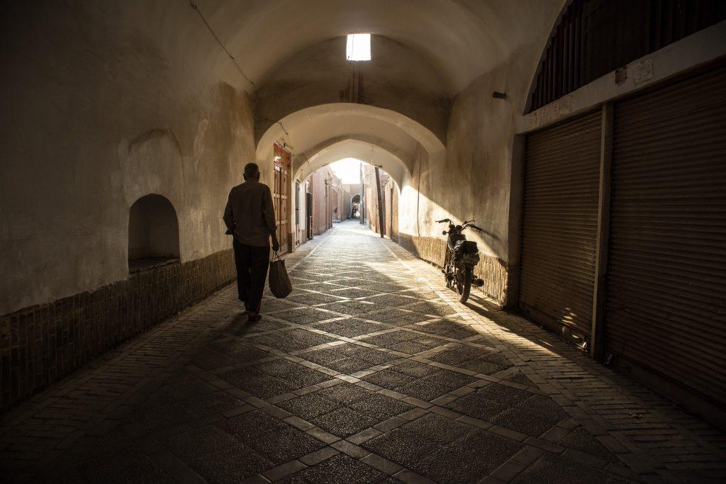 mężczyzna idzie wąską uliczką w yazd, w iranie.