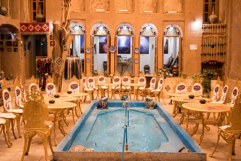 the inside of the tourist library in yazd: tables with chairs and a pool