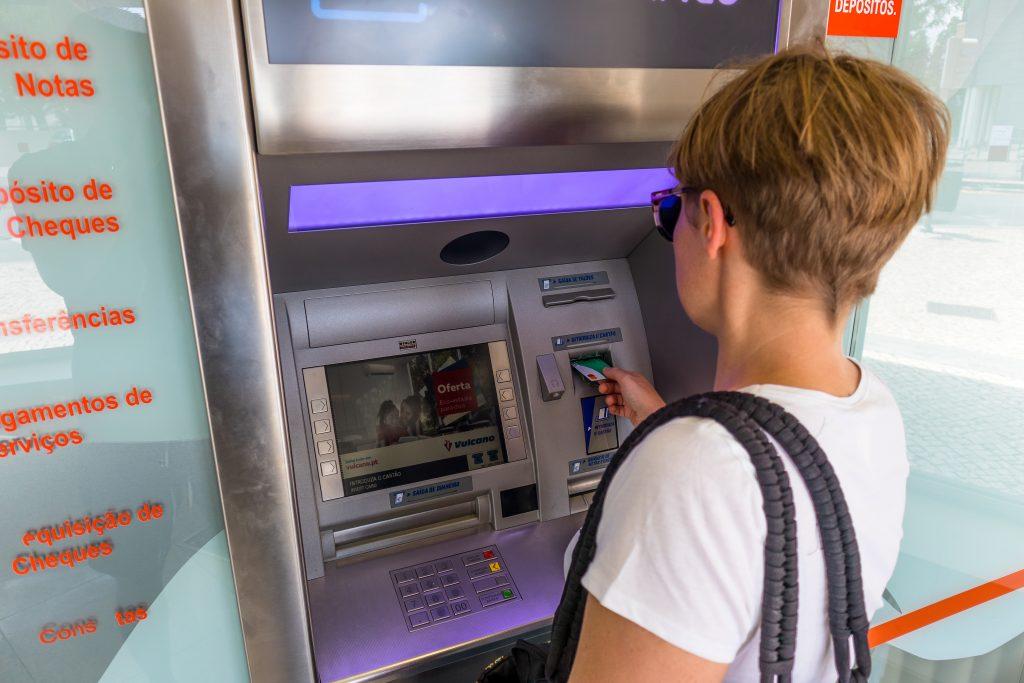 dziewczyna wyciąga gotówkę z bankomatu kartą monese w Portugalii