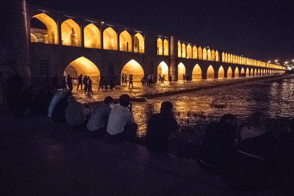 Ludzie siedzą nad rzeką przy oświetlonym moście w Esfahan.