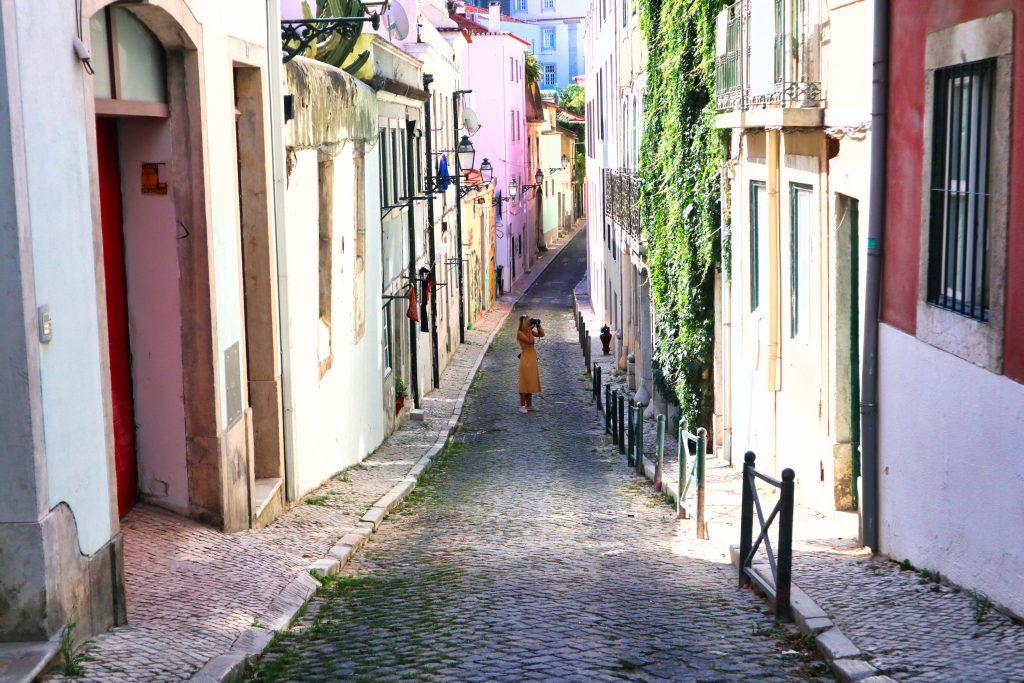 dziewczyna w żółtej sukience fotografuje ulice lizbony