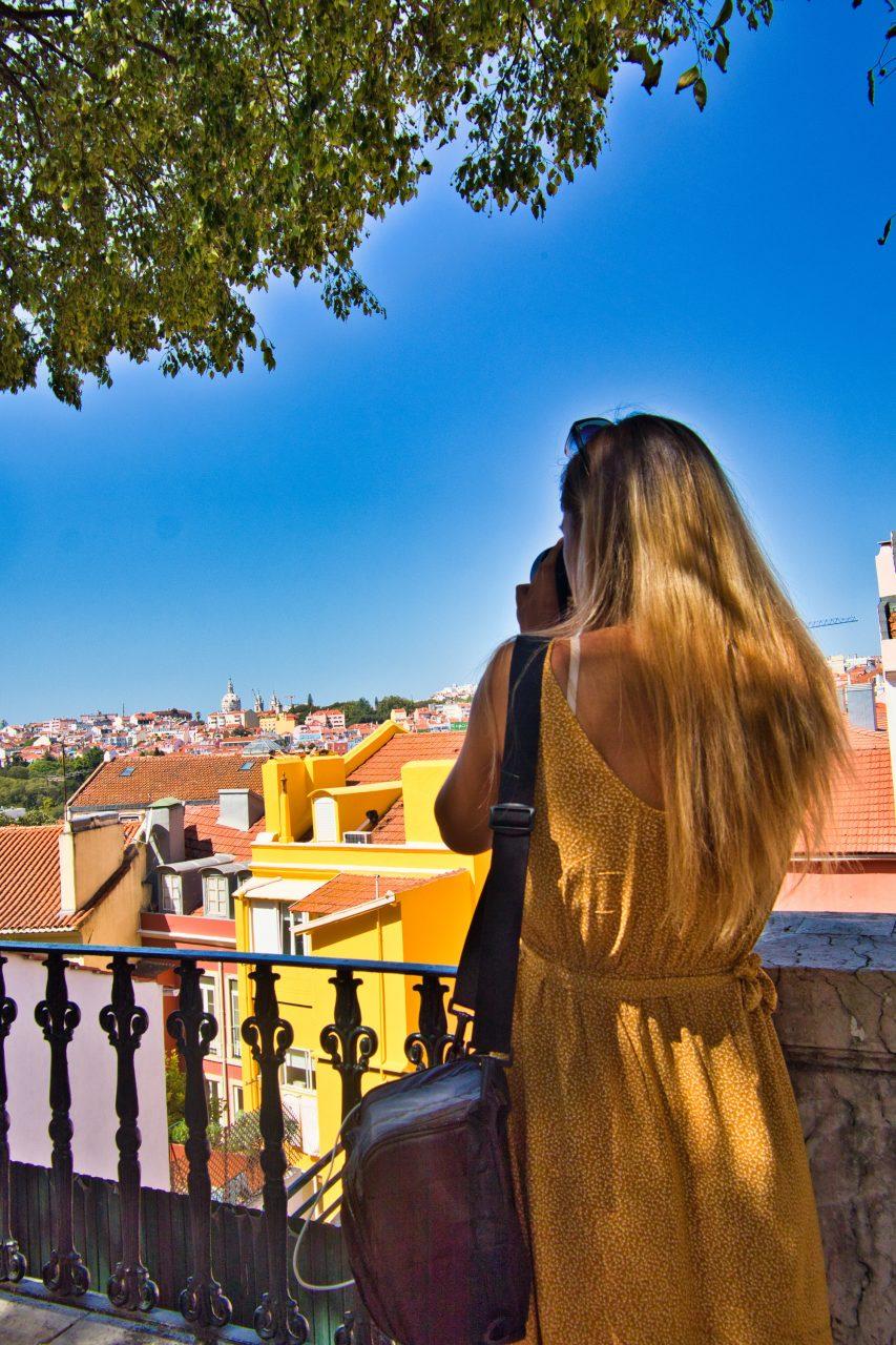 dziewczyna w żółtej sukience robi zdjęcia na spacerze po lizbonie
