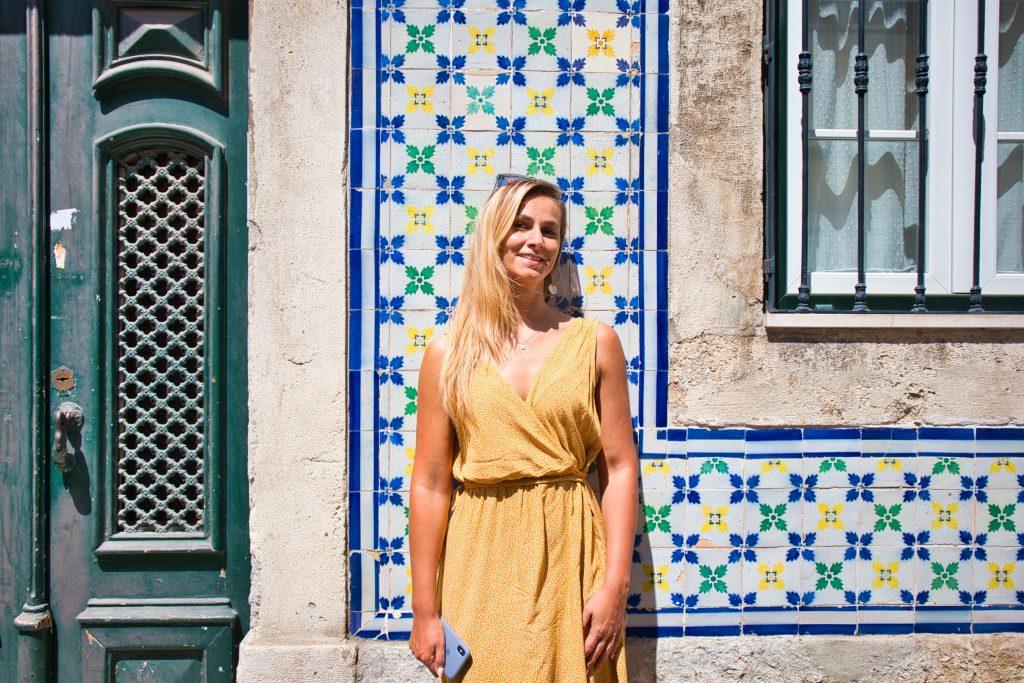 dziewczyna w żółtej sukience stoi na tle kolorowej ściany przed budynkiem w lizbonie