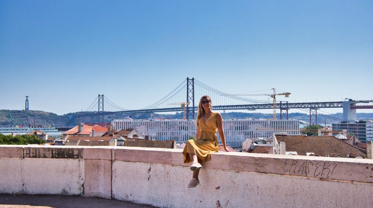 dziewczyna w żółtej sukience siedzi na murku w lizbonie