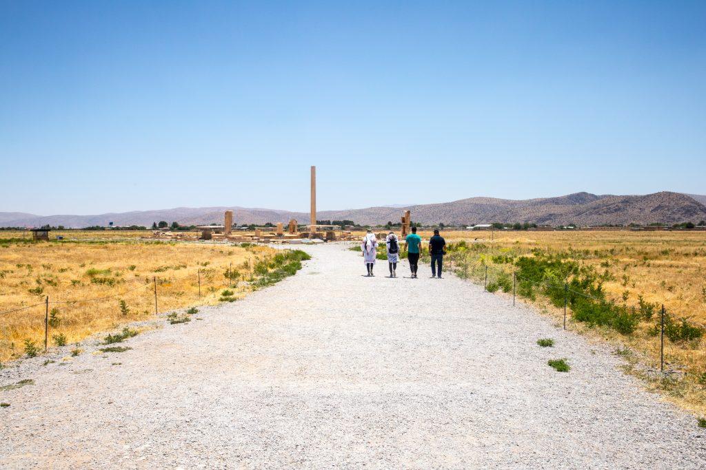 grupa ludzi idzie piaszczysta droga w pasargady w iranie