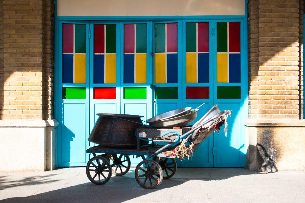 wozek z miotlami stoi przed kolorowym sklepem w shiraz, w iranie