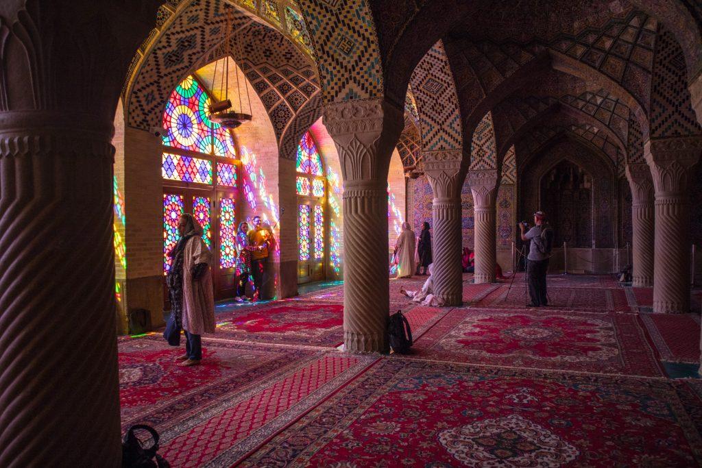 turyści w różowym meczecie przechadzają się po pomieszczeniu i robią zdjęcia