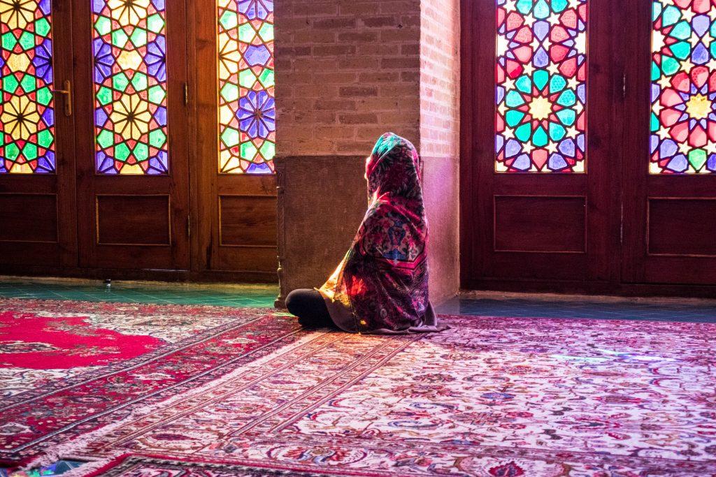 dziewczyna w hidżabie siedzi na podłodze w różowym meczecie w shiraz i patrzy zamyślona w stronę okna