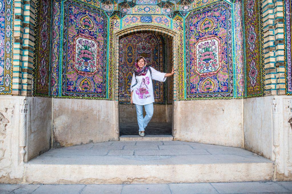dziewczyna stoi w rozowych drzwiach w meczecie w shiraz, w iranie.