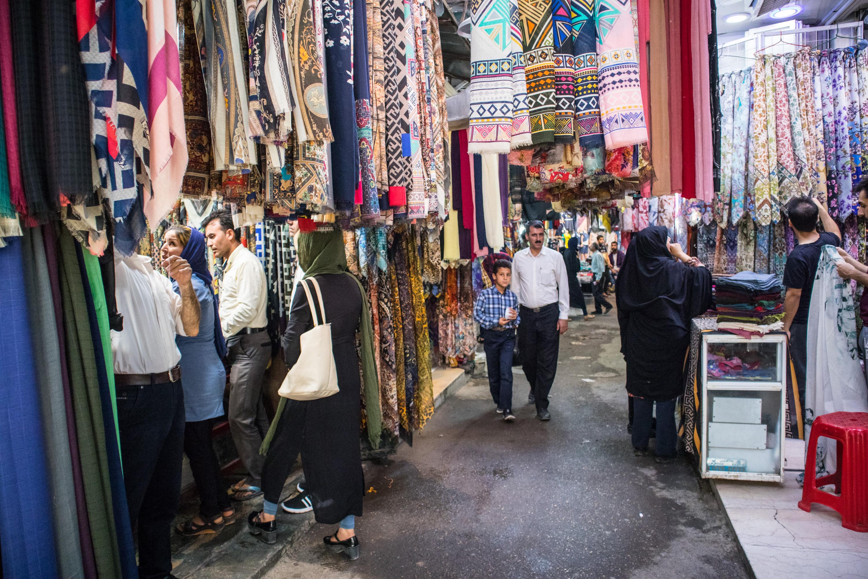 syn z ojcem przechadzają się po Vakil Bazar w Shiraz, w Iranie. Z sufitu zwisają chusty i dywany.