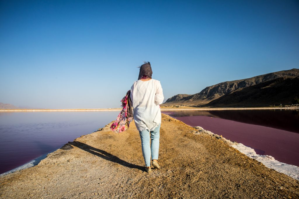 a girl walks on the maharloo lake in shiraz, iran