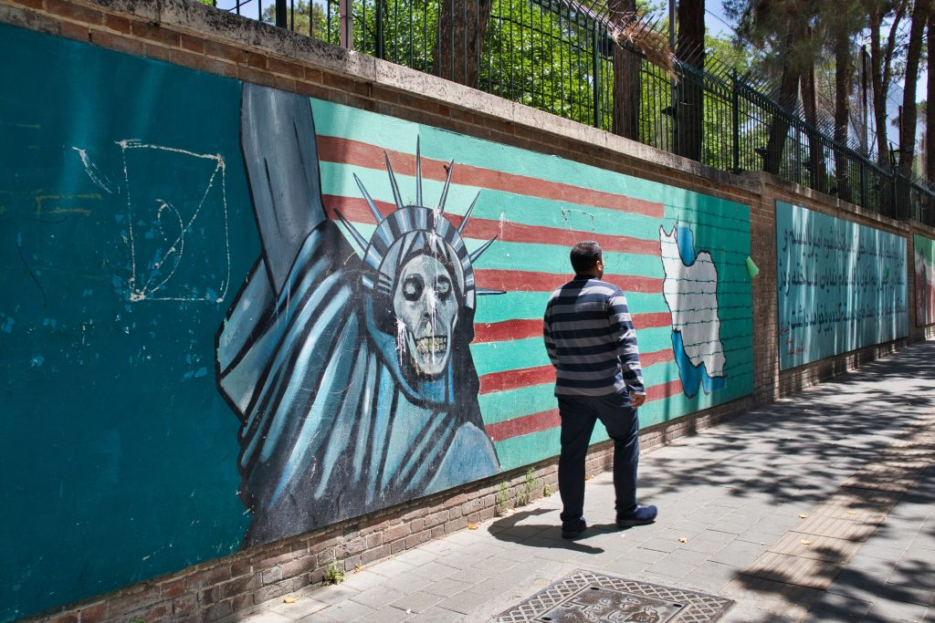 a man walks pass the former american embassy in teheran