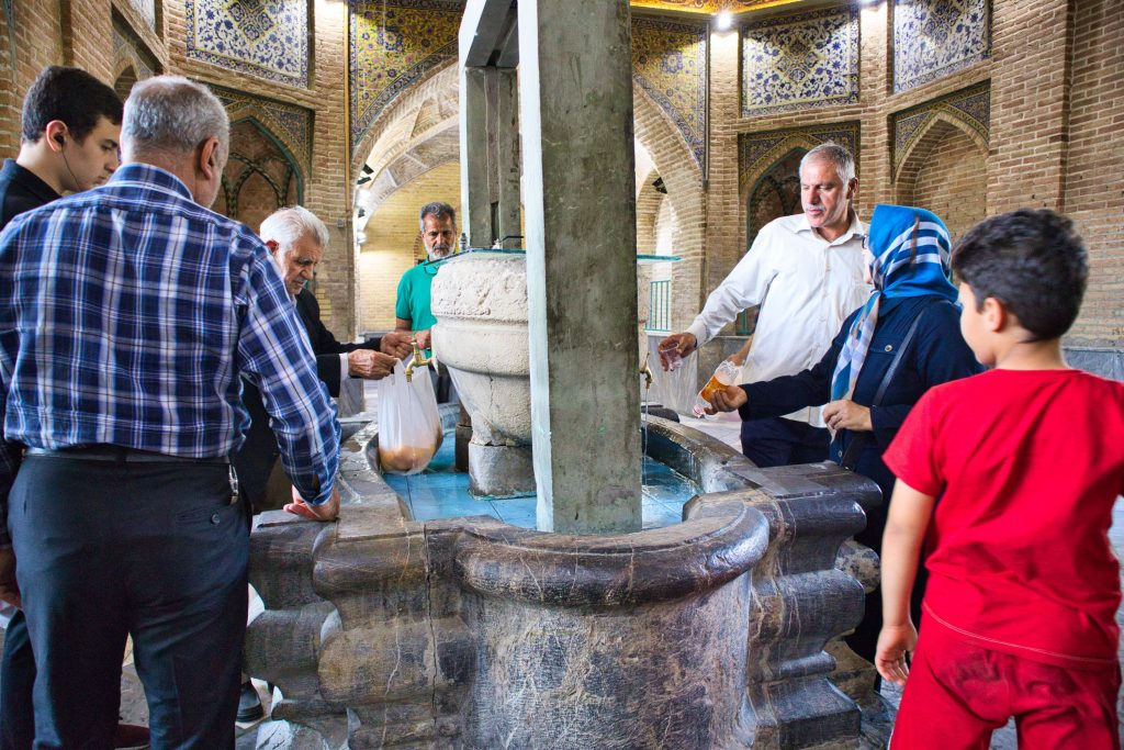 people standing at a well in grand bazaar in teheran