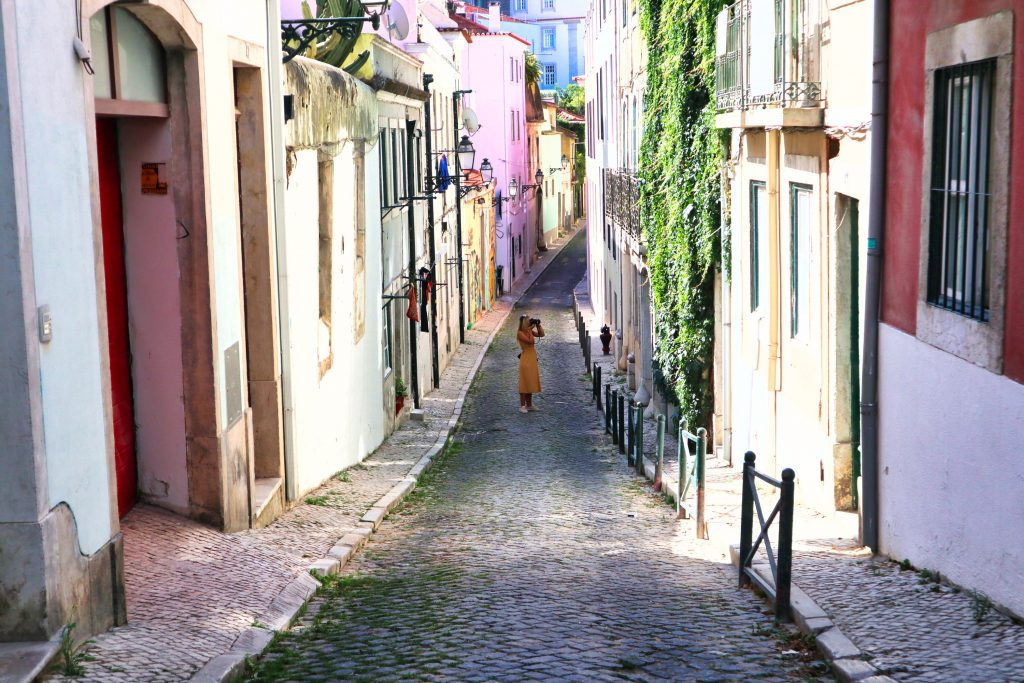 a girl in a yellow dress photographs a pink house in lisbon, portugal