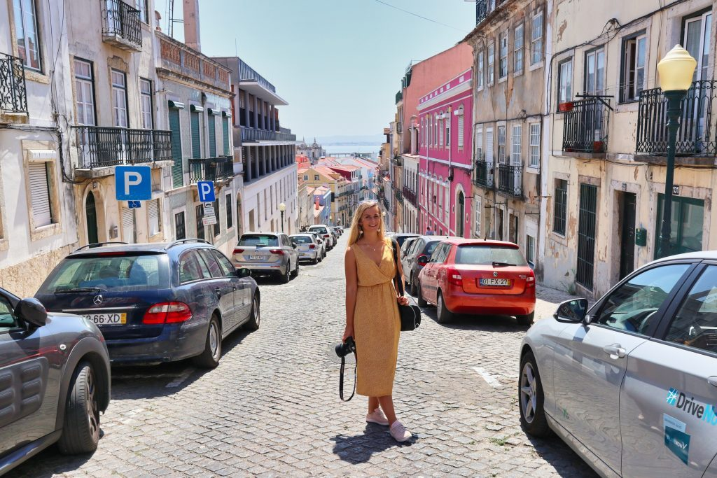 a girl in a yellow dress stands on a street of lisbon with colourful houses and smiles